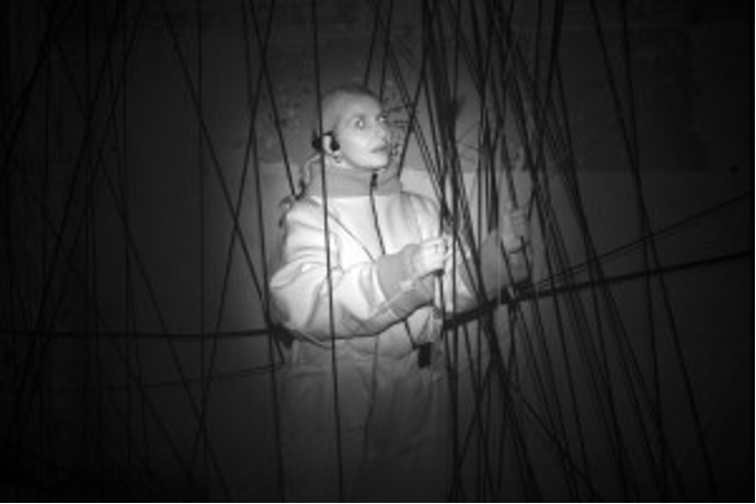 Infrared photo in the dark: An image of a woman trapped in ropes.
